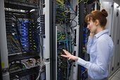 Technician talking on phone while analysing server in large data center