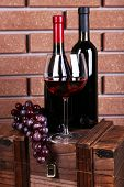 Bottle and glass of wine and ripe grape on box on brick wall background