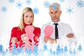 Couple not talking holding two halves of broken heart against snowflakes and fir trees
