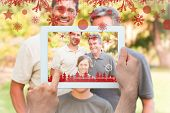 Hands holding tablet pc against family looking at the camera in the park