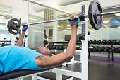 Side view of a determined young muscular man lifting barbell in gym