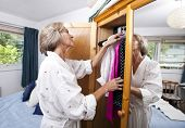 Senior woman selecting clothes from closet at home