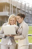 Happy young businesswomen using laptop together against building