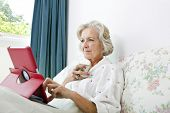 Senior woman using digital tablet while having coffee on bed at home