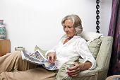 Senior woman reading newspaper while relaxing at home