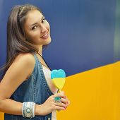 Young cheerful woman holding candy painted in colors of ukrainian flag. Ukrainian patriot concept. Toned.