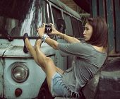 Urban girl has fun with vintage photo cameras outdoor near tree and retro car, image toned.