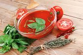 cold fresh diet tomato soup with basil thyme and raw tomatoes in transparent bowl over red mat on wo