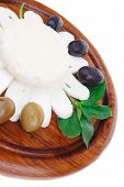 dairy products : feta white cheese sliced on cut board with olives and basil leaves isolated over wh