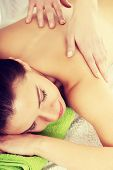 Beautiful woman lying on bed in spa salon having massage. Spa concept.