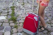 Travel concept. Red suitcase and legs of a young girl on the cobbles road.