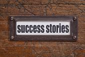 success stories - file cabinet label, bronze holder against grunge and scratched wood