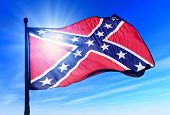 stock photo of flag confederate  - Confederate flag waving on the wind against the blue sky - JPG