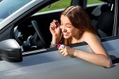 An Attractive Young Woman Drawing Eyelashes In The Rear View Mirror While Driving