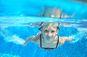 Happy active underwater kid swims in pool