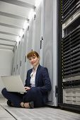 Technician sitting on floor beside server tower using laptop in large data center