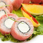 American Maki Sushi - Philadelphia Roll made of Cream Cheese  inside. Tuna outside. Served on Salad Leaf with Lemon Slice