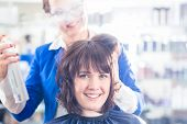 picture of hairspray  - Female coiffeur giving women hairstyling with hairspray in hairdresser shop - JPG