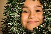 Cute little girl with tinsel around her head smiling at camera