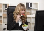 Businesswoman Having A Quick Snack At Her Desk