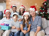 Extended family in Christmas hats with gift boxes in living room against snow falling