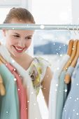 Beautiful female customer selecting clothes at store against snow falling