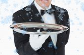 Smiling man holding a silver tray against snow falling