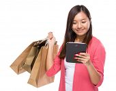 Woman with shopping bag and tablet