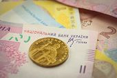 Bright ukrainian golden coin and banknotes macro background