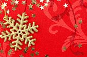Golden Snowflake and Stars - Christmas decoration on red ornamented background