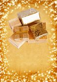 Gift Box In Gold Wrapping Paper On Vintage Cardboard Background With Glowing Stars