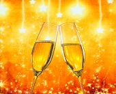 A Pair Of Champagne Flutes With Golden Bubbles On Golden Stars Light Background
