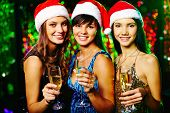 Three cheerful girls looking at camera with smiles at Christmas party