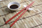Soy sauce in bowl with chopsticks on mat