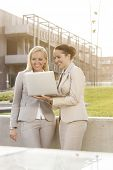 Happy young businesswomen using laptop together while standing against building