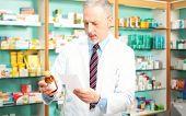 Senior pharmacist taking a bottle of pills