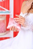 Bride in white dress and gloves holding decorative pillow with wedding rings, close-up, on bright background