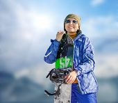 Young Woman With Snowboard On The Bright Blue Sky Background