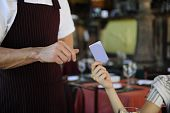 picture of debit card  - female customer paying with credit card at the restaurant - JPG