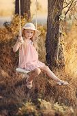 image of swing  - in the park near the big trees ride on a swing Pretty girl with long hair and a hat - JPG