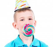 Smiling boy in blue t-shirt and party hat with colored candy - isolated on white.