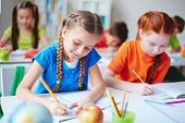 stock photo of diligent  - Diligent girls drawing with crayons at lesson - JPG