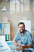 Bearded businessman in casualwear sitting at workplace