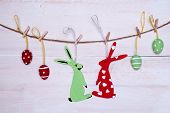 foto of easter eggs bunny  - A Couple Of Easter Bunnies One Female And One Red Easter Bunny With Hearts Hanging On A Line With Two Red And Two Green Easter Eggs Which Are Dotted And Striped On White Wooden Vintage Or Rustic Background For Easter Greetings And Happy Easter - JPG