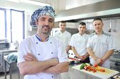 Handsome chef dressed in white uniform decorating pasta salad and seafood fish in modern kitchen