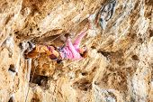 Young female rock climber on a cliff
