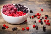 picture of frozen  - frozen berries in white plate on wooden background - JPG