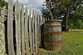 Wooden barrel near old fence