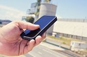 closeup of the hand of a man using a smartphone in an industrial park