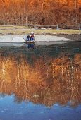 Children play on the banks of a pond of water natural